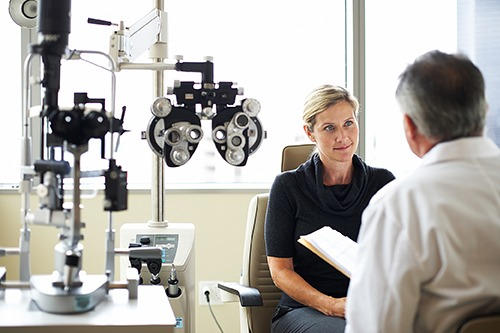 Female patient listening to male doctor, eye equipment on the left