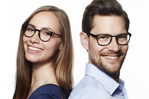 Man and woman wearing glasses smiling