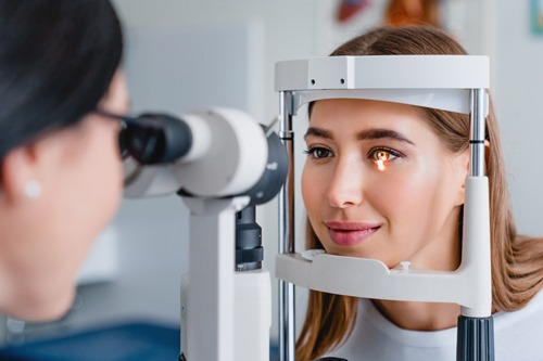 Woman's eye being examined by female doctor using equipment